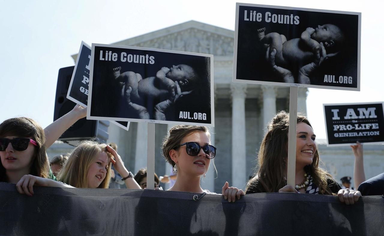 Anti-abortion demonstrators wait for the U.S. Supreme Court ruling in the Hobby Lobby case to be announced in Washington June 30, 2014. The U.S. Supreme Court on Monday ruled that business owners can object on religious grounds to a provision of U.S. President Barack Obama's healthcare law that requires closely held private companies to provide health insurance that covers birth control. REUTERS/Jonathan Ernst (UNITED STATES - Tags: CIVIL UNREST RELIGION POLITICS HEALTH)