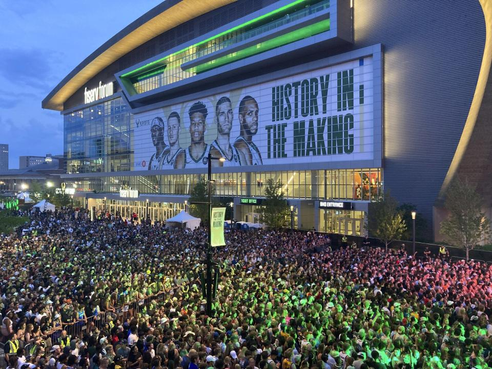 """Thousands of fans gather outside Fiserv Forum to watch on a video screen as the Milwaukee Bucks play at Phoenix in Game 1 of the NBA Finals on Monday, July 5, 2021, in Milwaukee. Bucks officials said 9,000 fans watched the game on a video screen inside Fiserv Forum and another 20,000 watched in the """"Deer District"""" outside the arena. The Bucks are in the Finals for the first time since 1974 as they chase their first championship since 1971. (AP Photo/Steve Megargee)"""