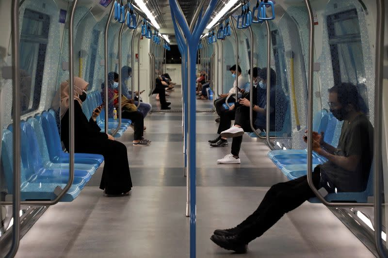 People wearing protective masks and following social distancing measures ride a Mass Rapid Transit train, in Kuala Lumpur
