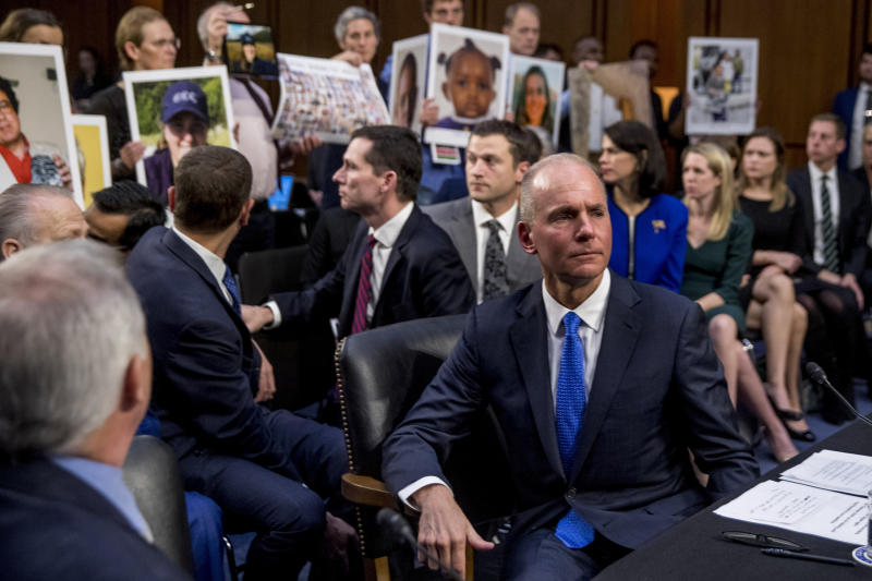Boeing Company President and Chief Executive Officer Dennis Muilenburg, right foreground, watches as family members hold up photographs of those killed in the Ethiopian Airlines Flight 302 and Lion Air Flight 610 crashes during a Senate Transportation Committee hearing on 'Aviation Safety and the Future of Boeing's 737 MAX' on Capitol Hill in Washington, Tuesday, Oct. 29, 2019. (AP Photo/Andrew Harnik)