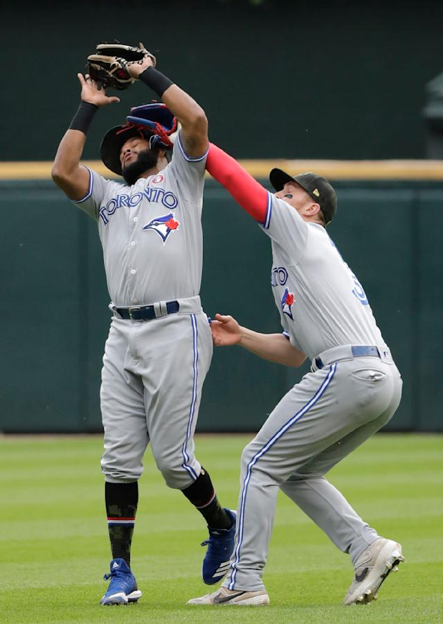 Toronto Blue Jays second baseman Richard Urena, left, and right fielder Brandon Drury collide as Urena makes a catch a fly ball by Chicago White Sox's James McCann during the third inning of a baseball game in Chicago, Saturday, May 18, 2019. (AP Photo/Nam Y. Huh)