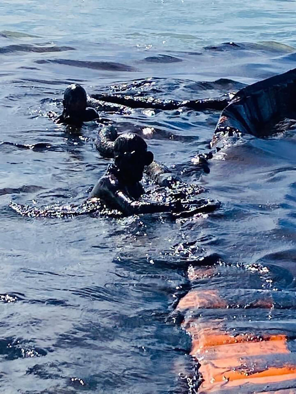 "This photo taken and provided by Georges de La Tremoille of Mu Press shows divers using a containment boom to help contain oil leaking from the MV Wakashio, a bulk carrier ship that recently ran aground off the southeast coast of Mauritius, Friday, Aug. 7, 2020. The Indian Ocean island of Mauritius declared a ""state of environmental emergency"" late Friday after a Japanese-owned ship that ran aground offshore days ago began spilling tons of fuel. (Georges de La Tremoille/MU Press via AP)"