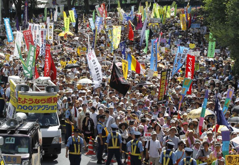 "Anti-nuclear energy protesters march on a street in Tokyo Monday, July 16, 2012. Tens of thousands of people gathered at a Tokyo park, demanding ""Sayonara,"" or goodbye, to nuclear power as Japan prepares to restart yet another reactor, and expressed outrage over a report that blamed culture on the Fukushima disaster. (AP Photo/Koji Sasahara)"