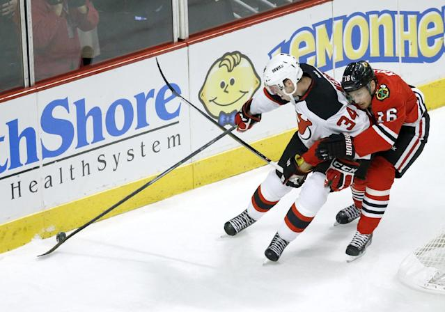 New Jersey Devils defenseman Jon Merrill (34) keeps Chicago Blackhawks center Marcus Kruger (16) from the puck during the first period of an NHL hockey game Monday, Dec. 23, 2013, in Chicago. (AP Photo/Charles Rex Arbogast)