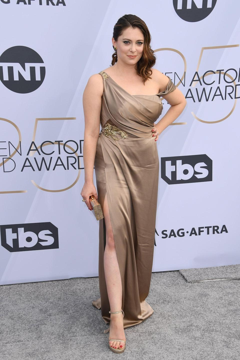<p>Wearing a gold off-the-shoulder dress by Cristina Ottaviano with matching heels.</p>