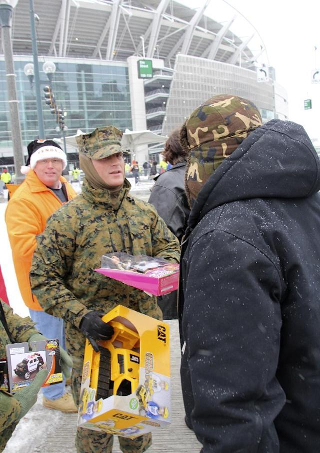Lance Sgt. Jesse Mooven collects toys outside Paul Brown Stadium prior to an NFL football game between the Cincinnati Bengals and the Indianapolis Colts, Sunday, Dec. 8, 2013, in Cincinnati. (AP Photo/Tom Uhlman)
