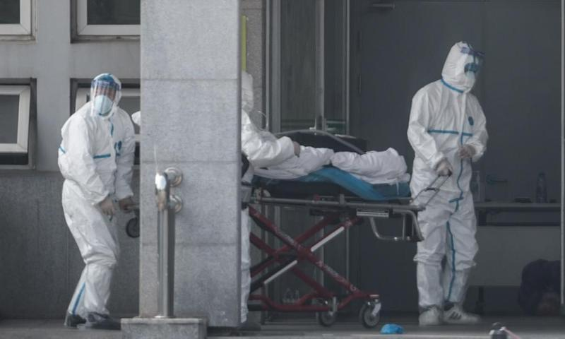 Medical staff in biohazard suits carry a patient into the Wuhan hospital where patients infected with the new strain of coronavirus are being treated.