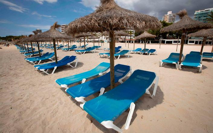 Empty deck chairs are pictured at Magaluf beach, Calvia, in Spain's Balearic island of Majorca - AFP