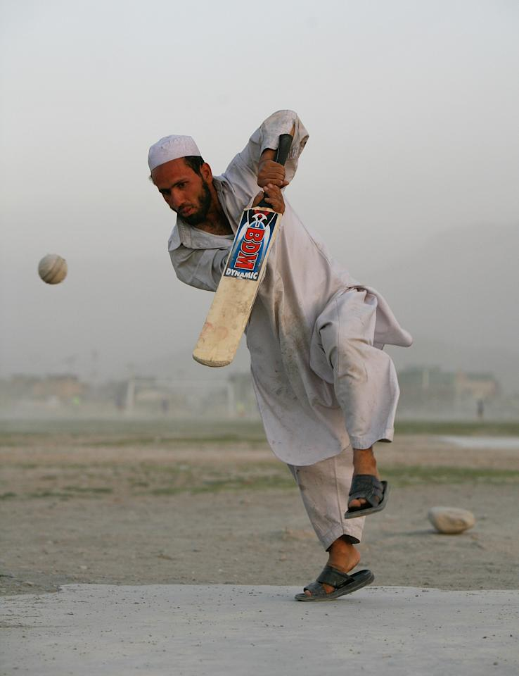 KABUL, AFGHANISTAN - JULY 27:  An Afghan cricket player hits the ball during a local league game July 27, 2007 Kabul, Afghanistan. After the fall of the Taliban when the refugees returned from camps in Pakistan they came back having learned a new sport, Cricket. There are now leagues spread across the country playing in dusty fields. For the average Afghan team the equipment is cheap but the uniforms are not afforable so they play in sandals and their traditional shawal kamis.  (photo by Paula Bronstein /Getty Images)