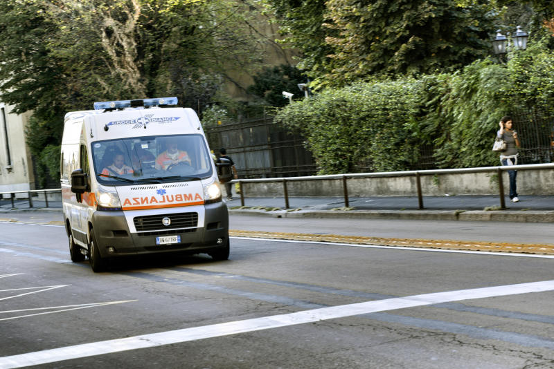 Milan, Italy - September 14, 2012: An ambulance with three paramedics is running fast in Milan city centre street for an emergency call. A woman on the right is walking and looking at her mobile phone.