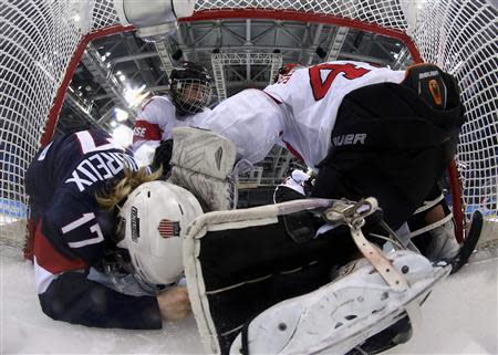 Team USA's Jocelyne Lamoureux (17) crashes into Switzerland's goalie Florence Schelling (R) as Switzerland's Laura Benz defends during the third period of their women's preliminary round hockey game at the Sochi 2014 Winter Olympic Games February 10, 2014. REUTERS/Martin Rose/Pool