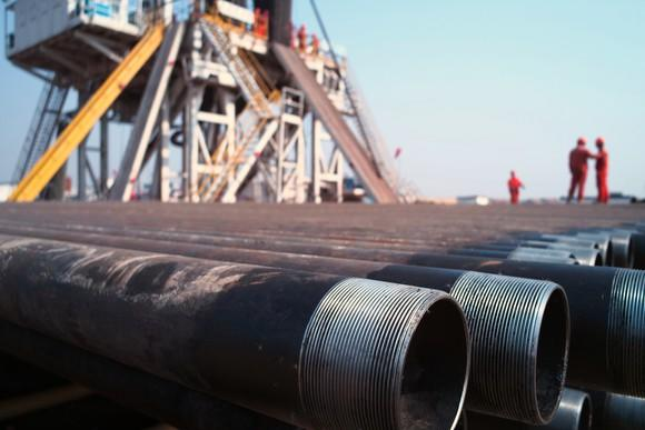 A close-up of drill pipes with people in hard hats and a rig in the background.