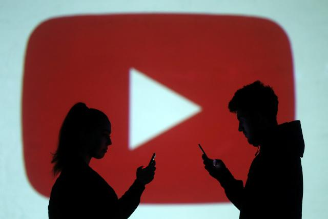 Silhouettes of mobile users are seen next to a screen projection of Youtube logo in this picture illustration taken March 28, 2018. REUTERS/Dado Ruvic/Illustration - RC1B4475F2D0