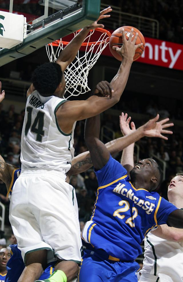 Michigan State's Gary Harris (14) and McNeese State's Ledrick Eackles (22) fight for a rebound during the first half of an NCAA college basketball game, Friday, Nov. 8, 2013, in East Lansing, Mich. (AP Photo/Al Goldis)