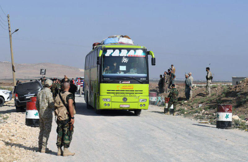 This photo released by the Syrian official news agency SANA, shows Syrian troops overseeing the evacuation of people in buses from the two pro-government villages of Foua and Kfarya, at Tel el-Eis, the crossing between Aleppo and Idlib provinces, Syria, Thursday, July 19, 2018. Over 7,000 people from the villages in the country's northwest that were besieged by the rebels for three years have been evacuated, Syria's state-run media reported Thursday. (SANA via AP)
