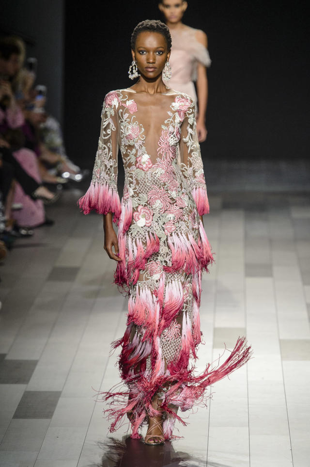 <p><i>Model wears rose-embellished and fringed dress from the SS18 Marchesa collection. (Photo: ImaxTree) </i></p>