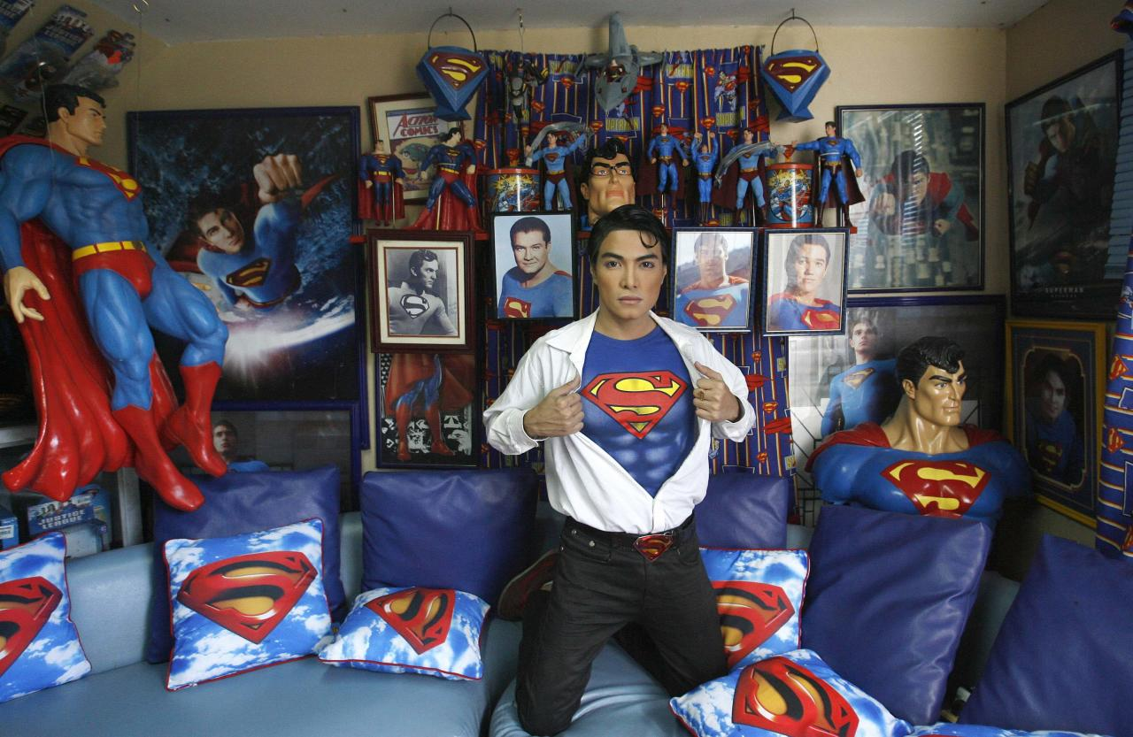 "Herbert Chavez poses with his Superman memorabilia inside his house in Calamba Laguna, south of Manila October 12, 2011. In his idolization of the superhero, Chavez, a self-professed ""pageant trainer"" who owns two costume stores, has undergone a series of cosmetic surgeries for his nose, cheeks, lips and chin down to his thighs and even his skin color to look more like the ""Man of Steel"". The final result bears little resemblance to his old self. REUTERS/Cheryl Ravelo (PHILIPPINES - Tags: SOCIETY)"