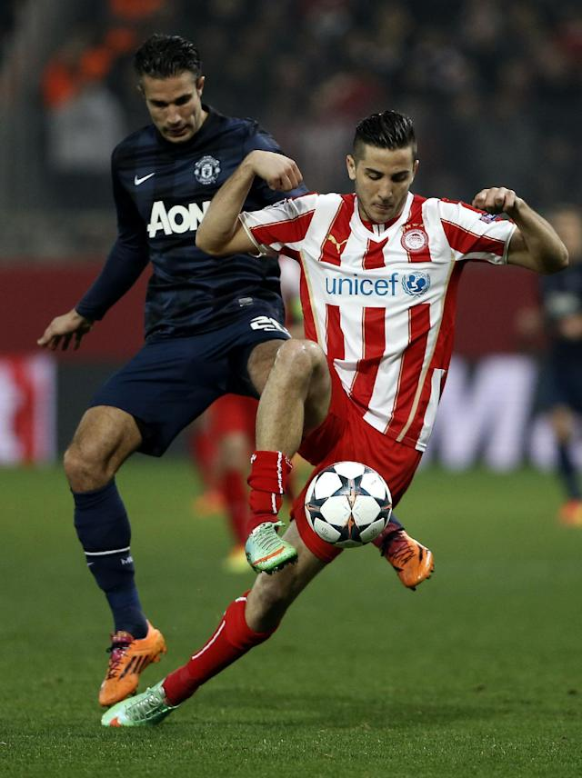 Olympiakos' Kostas Manolas, right, fights for the ball with Manchester United's Robin Van Persie during their Champions League, round of 16, first leg soccer match at Georgios Karaiskakis stadium, in Piraeus port, near Athens, on Tuesday, Feb. 25, 2014. (AP Photo/Petros Giannakouris)