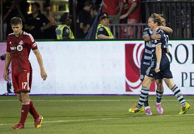 Sporting Kansas City forward Jacob Peterson, right, celebrates his soccer game-winning goal as Toronto FC defender Nick Hagglund, left, walks past during second-half MLS action in Toronto, Saturday, July 26, 2014. (AP Photo/The Canadian Press, Nathan Denette)