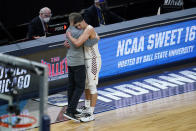 Loyola Chicago head coach Porter Moser, left, hugs guard Lucas Williamson after a Sweet 16 game against Oregon State in the NCAA men's college basketball tournament at Bankers Life Fieldhouse, Saturday, March 27, 2021, in Indianapolis. Oregon State won 65-58. (AP Photo/Darron Cummings)
