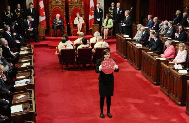 Page Brigette DePape stands in the middle of the floor of the Senate as Governor General David Johnston delivers the Speech from the Throne in the Senate Chamber on Parliament Hill in Ottawa on June 3, 2011.