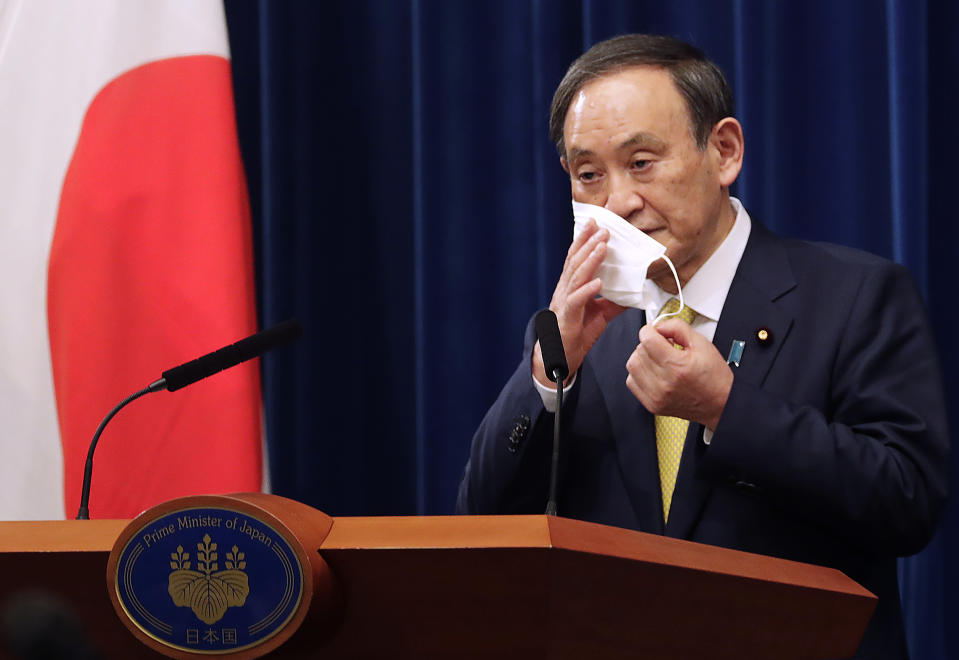 FILE - In this Dec. 4, 2020, file photo, Japanese Prime Minister Yoshihide Suga removes his face mask during a news conference in Tokyo. Opposition to the Tokyo Olympics is growing with calls for a cancellation as virus cases rise in Japan. The International Olympic Committee and local organizers have already said another postponement is impossible, leaving cancellation, or going ahead, as the only options. (AP Photo/Hiro Komae, Pool, File)