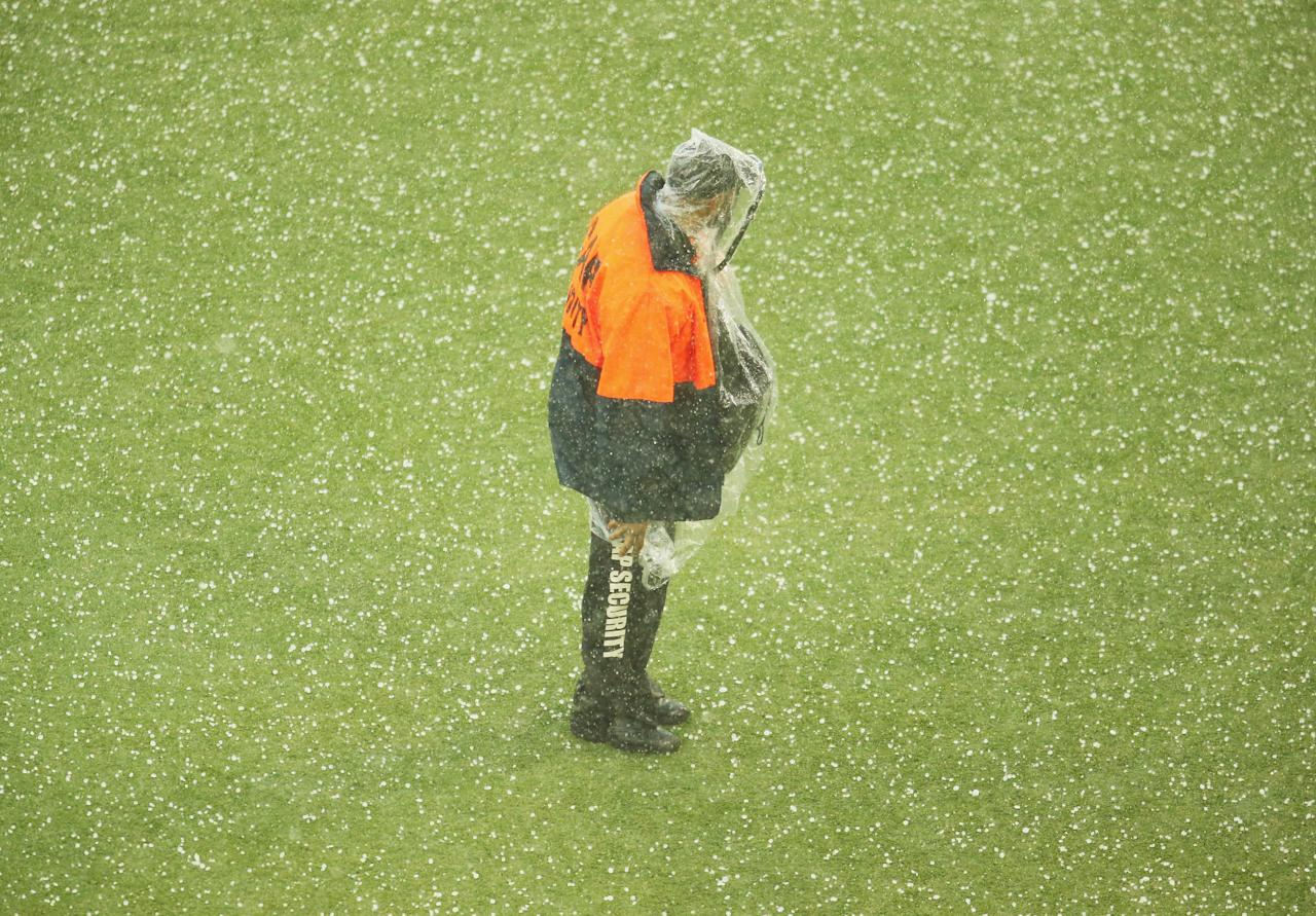 BRISBANE, AUSTRALIA - NOVEMBER 24:  A security guard looks on as it hails during day four of the First Ashes Test match between Australia and England at The Gabba on November 24, 2013 in Brisbane, Australia.  (Photo by Scott Barbour/Getty Images)