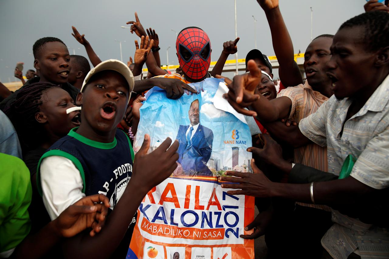 <p>People react as they hold a poster depicting Kenyan opposition leader Raila Odinga, the presidential candidate of the National Super Alliance (NASA) coalition, in Kisumu, Kenya, Aug.10, 2017. (Photo: Baz Ratner/Reuters) </p>
