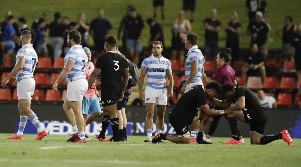 New Zealand's Ardie Savea and teammate Caleb Clarke, right, kneel and pray following the Tri-Nations rugby test between Argentina and the All Blacks in Newcastle, Australia, Saturday, Nov. 28, 2020. (AP Photo/Rick Rycroft)