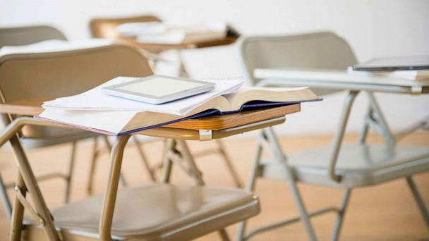 PHOTO: Digital tablet and book on desk in classroom. empty desks (STOCK PHOTO/Getty Images)