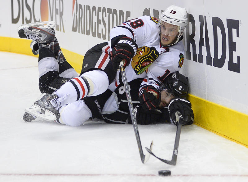 Chicago Blackhawks center Jonathan Toews (19) collides with Los Angeles Kings defenseman Drew Doughty (8) as they reach for the puck during the third period of Game 3 of the NHL hockey Stanley Cup playoffs Western Conference finals, Tuesday, June 4, 2013, in Los Angeles. (AP Photo/Mark J. Terrill)