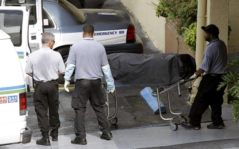 Miami-Dade morgue workers carry out a body out at the scene of a fatal shooting in Hialeah, Fla., Saturday, July 27, 2013. A gunman holding hostages inside the apartment complex killed six people before being shot to death by a SWAT team that stormed the building early Saturday following an hours-long standoff, police said. (AP Photo/Alan Diaz)