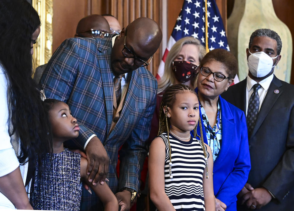Philonise Floyd, George Floyd's brother, looks down at Gianna Floyd, George Floyd's daughter, while while standing with members of the Floyd family prior to a meeting to mark the anniversary of the death of George Floyd with House Speaker Nancy Pelosi, D-Calif., Tuesday, May 25, 2021 at the Capitol in Washington. (Erin Scott/Pool via AP)