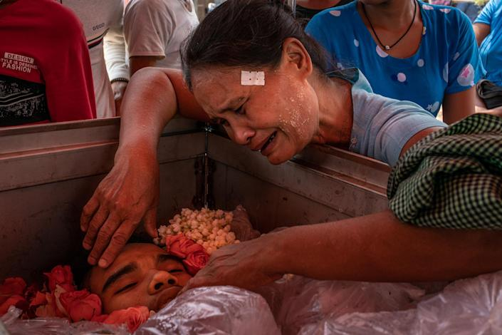"""The mother of Aung Zay Min, a 20-year-old who was shot and killed by security forces, mourns over his body at his funeral in Dala township, outside Yangon, Myanmar, on March 27, 2021.<span class=""""copyright"""">Getty Images</span>"""