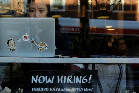 "FILE PHOTO: A ""Now Hiring"" sign sits in the window of Tatte Bakery and Cafe in Cambridge, Massachusetts, U.S., February 11, 2019. REUTERS/Brian Snyder/File Photo"