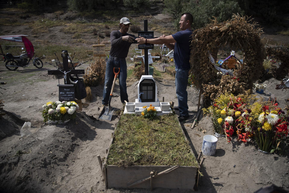 "Cemetery worker Jorge Arvizu, left, helps a family member place a plaque on the grave of Vicente Dominguez who died of complications related to the new coronavirus, at the municipal cemetery Valle de Chalco, on the outskirts of Mexico City, Tuesday, Oct. 20, 2020. Mexican families traditionally flock to local cemeteries to honor their dead relatives as part of the ""Dia de los Muertos,"" or Day of the Dead celebrations, but according to authorities the cemeteries will be closed this year to help curb the spread of COVID-19. (AP Photo/Marco Ugarte)"