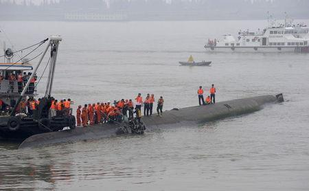 A woman is rescued by divers after a ship sank at the Jianli section of the Yangtze River, Hubei province, China, June 2, 2015. REUTERS/China Daily