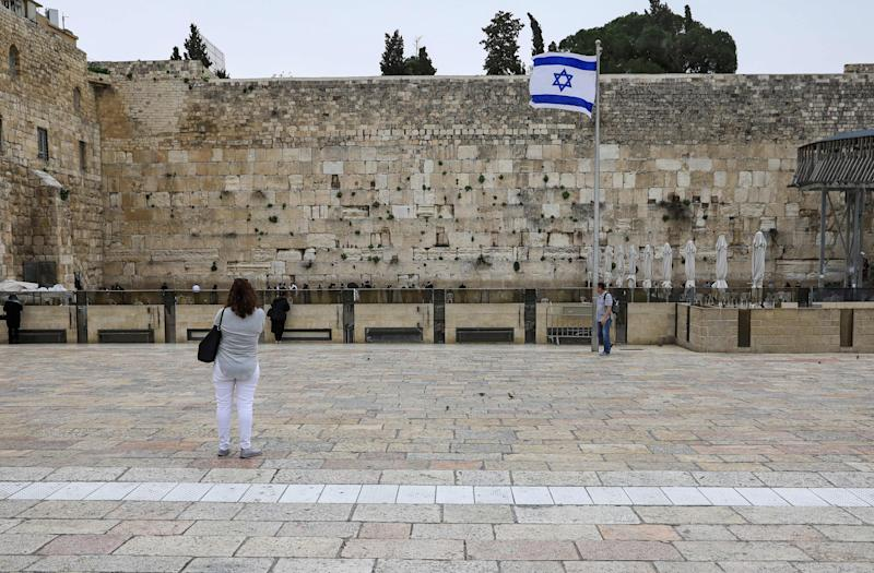 A tourist looks at the nearly deserted Western Wall, Judaism's holiest site, after Israel has imposed some of the world's tightest restrictions to contain COVID-19 coronavirus disease, in Jerusalem on March 12, 2020. - Israel imposed a two-week quarantine on all travellers entering the country, almost stopping tourism and limiting public gatherings as officials confirmed its 100th case of the COVID-19 coronavirus disease. (Photo by Emmanuel DUNAND / AFP) (Photo by EMMANUEL DUNAND/AFP via Getty Images)