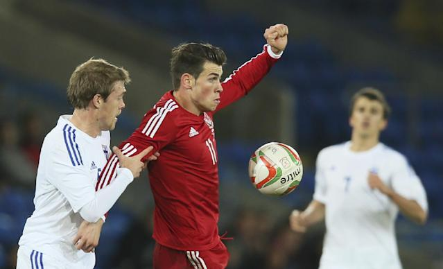 Wales' Gareth Bale, right, holds off the challenge of Finland's Veli Lampi during their international friendly soccer match in Cardiff, Wales, Saturday, Nov. 16, 2013. (AP Photo/Alastair Grant)