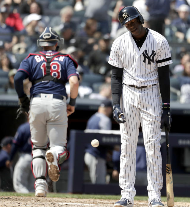 New York Yankees' Cameron Maybin, right, reacts after striking out looking as Minnesota Twins as catcher Mitch Garver (18) runs to the dugout at the end of the fourth inning of a baseball game, Saturday, May 4, 2019, in New York. (AP Photo/Julio Cortez)