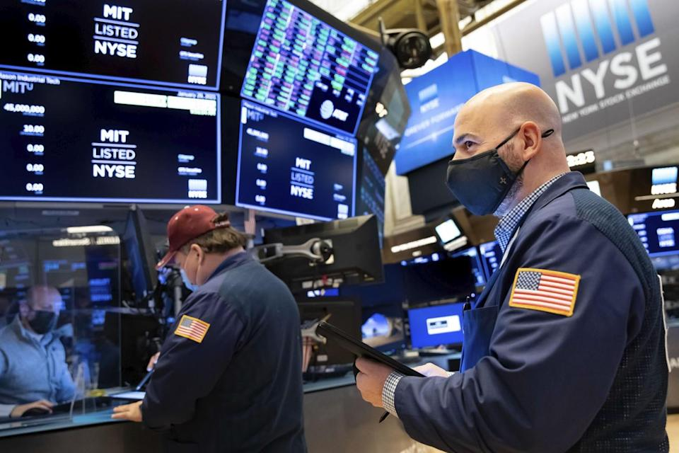 Trader Fred Demarco, right, works on the floor at the NYSE on Friday.