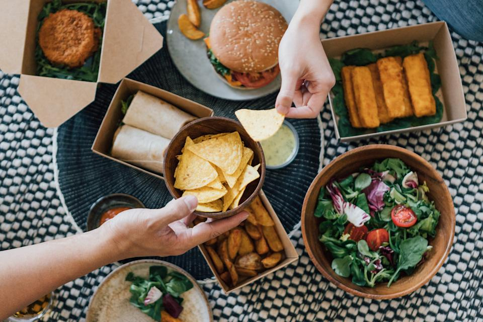 Flat lay view of couple sharing delicious takeaway fast food meal - with burger, wrap sandwich, fish cake, fish sticks, potato wedges and vegetable salad.