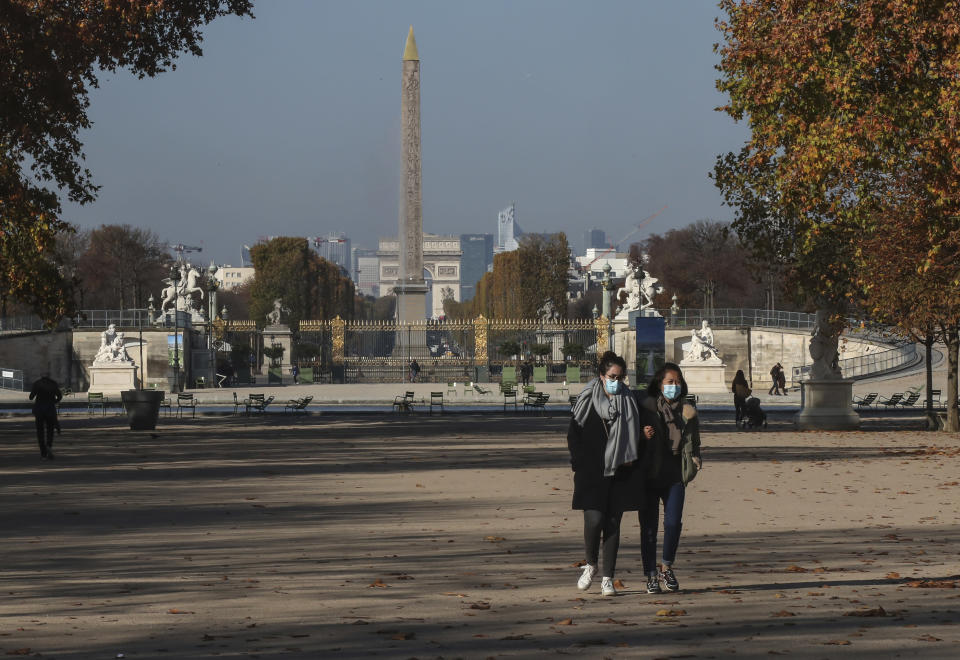 Women wearing face masks as a precaution against the coronavirus walk through the Tuileries garden in Paris, Friday, Nov. 6, 2020. The French government is supplying quick virus tests to nursing homes around the country, amid sharply rising numbers of virus infections and deaths in care homes in recent weeks. Arc de Triomphe and Obelisk in the background. (AP Photos/Michel Euler)
