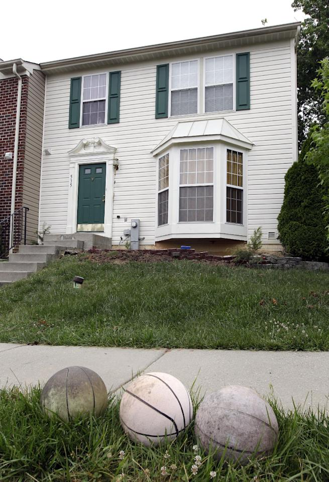 Old basketballs sit on the curb outside of a house in Joppatowne, Md., Friday, June 1, 2012, where a 21-year-old college student accused of killing a housemate told police he ate the victim's heart and part of his brain after he died. Alexander Kinyua, a Kenya native, is charged with first-degree murder and other charges in the death of 37-year-old Kujoe Bonsafo Agyei-Kodie. (AP Photo/Patrick Semansky)