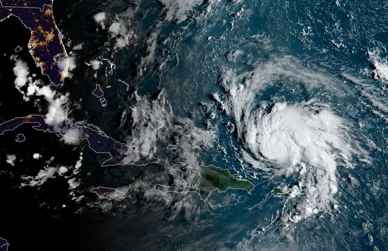 This satellite image obtained from NOAA/RAMMB, shows Hurricane Dorian (R) as it passes Puerto Rico at 11:30 central time on August 29, 2019. The National Hurricane Center (NHC) in Miami said the hurricane watch and tropical storm warning for the island had been lifted, and that