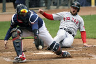 Boston Red Sox Christian Arroyo (39) slides safely into home base after Boston Red Sox Bobby Dalbec (29) hit a sharp line drive against the Minnesota Twins during the fifth inning of a baseball game, Tuesday, April 13, 2021, in Minneapolis. Boston won 4-2. (AP Photo/Stacy Bengs)