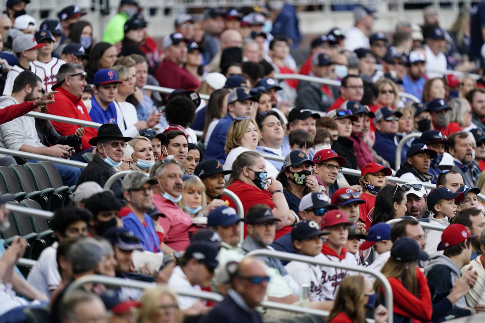 Baseball fans watch a game between the Philadelphia Phillies and the Atlanta Braves, Friday, May 7, 2021, in Atlanta. The Braves opened the stadium to 100% capacity. (AP Photo/John Bazemore)