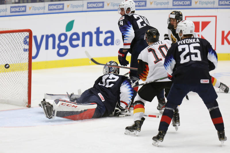 From left, USA goalkeeper Dustin Wolf, Mattias Samuelsson, Germany's Justin Schuetz and Jacob Pivonka of the USA in action during the 2020 IIHF World Junior Ice Hockey Championships Group B match between Germany and USA in Ostrava, Czech Republic, Friday Dec. 27, 2019. (Petr Sznapka/CTK via AP)