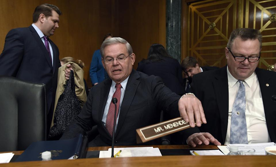 Senate Banking Committee member Sen. Robert Menendez, D-N.J., center, sitting next to Sen. Jon Tester, D-Mont., right, arrives for the committee's hearing on Iran sanctions, Tuesday, Jan. 27, 2015, on Capitol Hill in Washington. (Susan Walsh/AP Photo)