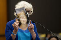 Dolly Kreis holds a photo of her daughter Debbie Strauss and shows it to Joseph James DeAngelo, known as the Golden State Killer, who did not look back, during the first day of victim impact statements Tuesday, Aug. 18, 2020, in Sacramento, Calif. DeAngelo will be formally sentenced to life in prison on Friday. Strauss, who was raped by DeAngelo in 1977, died from cancer in 2016. (Santiago Mejia/San Francisco Chronicle via AP, Pool)